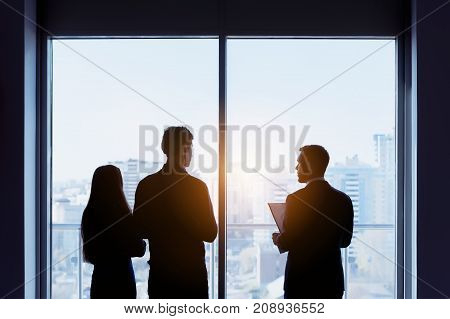 Couple and real estate agent stands near window and speaks before signing contract. Business concept
