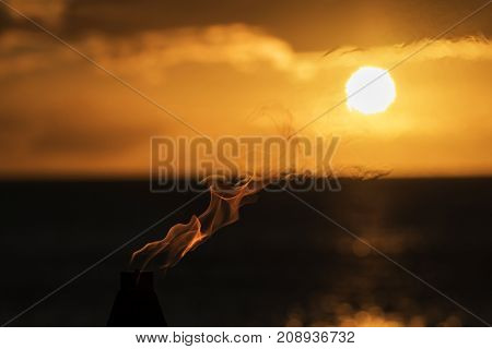 Flame from Torch Floats into Setting Sun Over Ocean