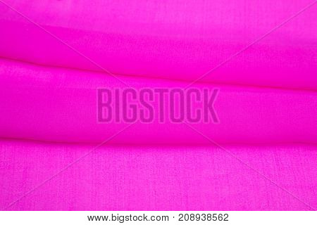 background image of a pink light fabric folded, artificial silk