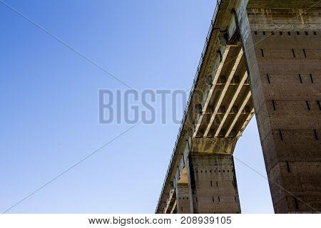 Under the bridge view in a blue sky. Concrete structure.