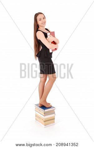 Education people teenager and school concept - teenager school girl standing on stack of books. Isolated over white