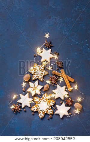 Christmas cookies in the shape of a tree with lights on an abstract painted blue background