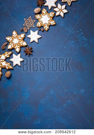 Christmas background corner border with cookies and spices on an abstract painted blue backdrop.