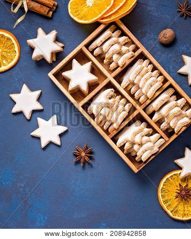 Traditional German Star Cookies in a gift box with spices and dried oranges over a blue background. Christmas or Yom Kippur.