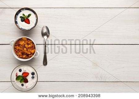 Healthy breakfast meals on wooden table copy space. Cornflakes and yogurt with berries and spoon, top view
