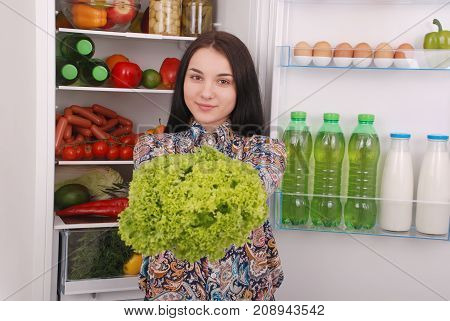 Healthy eating concept. Diet. Beautiful young girl near the Fridge with healthy food. Fruits and vegetables in the refrigerator. Vegan food