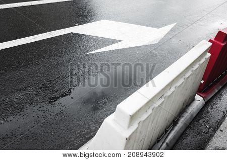 Wet Urban Street With Arrow Road Marking
