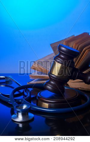 Wooden law gavel with stethoscope and book - medical law and justice concept