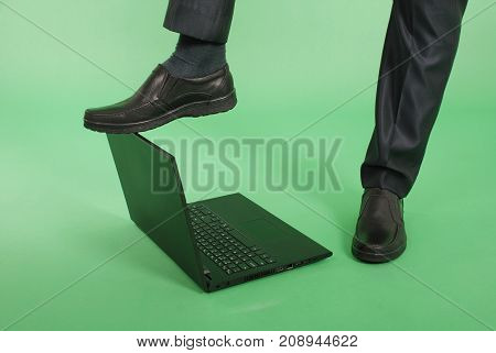 Full length portrait of confident mature businessman which keeps the foot on the laptop in formals standing isolated over green background. Close-up