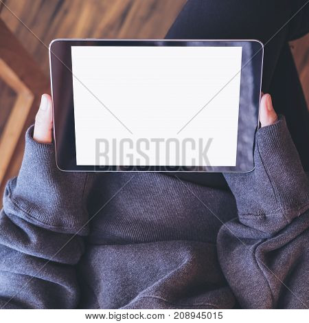 Mockup top view image of a woman sitting cross legged and holding black tablet pc with blank white screen on thigh and wooden floor background
