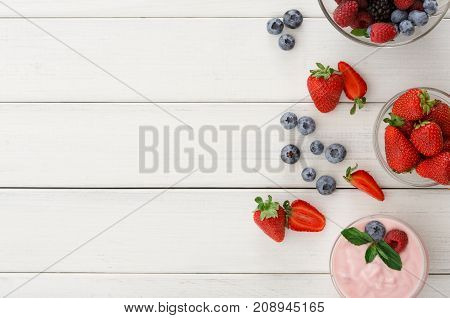 Tasty breakfast with greek yogurt, fresh strawberries, raspberries, blueberries and blackberries. Low fat morning meals and healthy start of the day. Detox and diet concept, copy space, top view