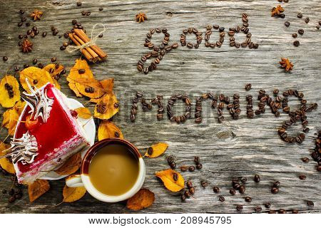 Good morning from coffee beans. A cup of coffee and a cake on a wooden background strewn with autumn yellow leaves and anise. Greeting for breakfast. View from above