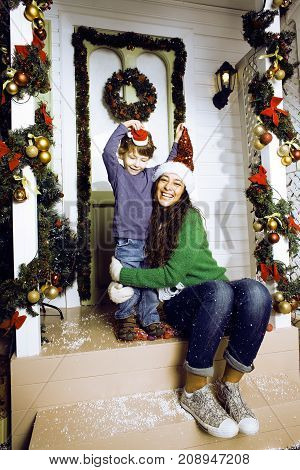 happy family on Christmas in red hats waiting gests and smiling outdoor at house