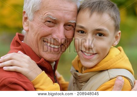 Portrait of happy grandfather and grandson in park