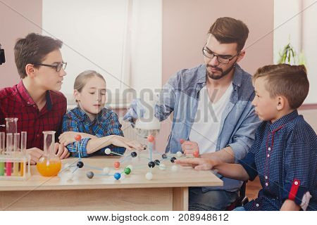 Stem education. Group of kids with teacher doing chemical experiment with liquid nitrogen in laboratory, copy space. Early development concept