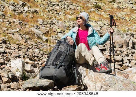 A tourist girl wearing sunglasses down jacket and hat with a backpack and mountain equipment with handles for tracking in her hands is sitting and relaxing looking at the beautiful view of the high mountain lake in the North Caucasus. Karachay-Cherkess