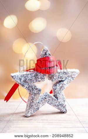Christmas Card with festive star snow and red ribbon on abstract defocused bokeh background. Christmas