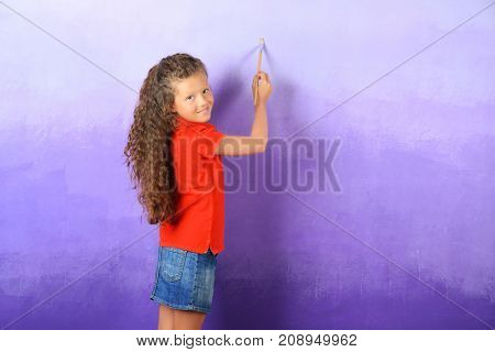 Little cute girl painting wall