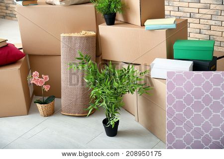 Carton boxes and interior items on floor in room. Moving house concept
