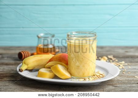 Jar with protein shake and plate with fruits on table