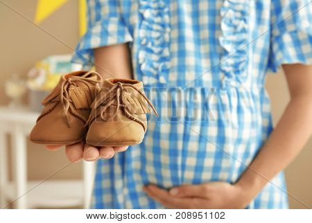 Pregnant woman holding baby shoes at party indoors