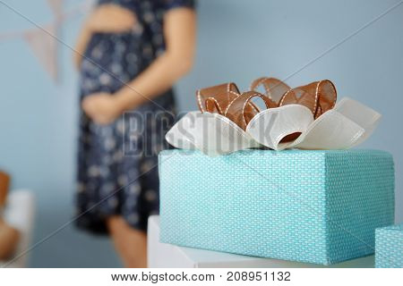 Baby shower gift and blurred pregnant woman indoors