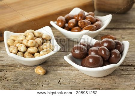 candies almonds, pecan and macadamia nuts in small bowl on rustic table