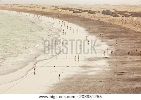 People at the Playa del Ingles beach, Grand Canary, Dunes of Maspalomas in background