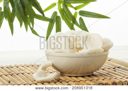 Shrimp crackers in bowl with bamboo leaves in background