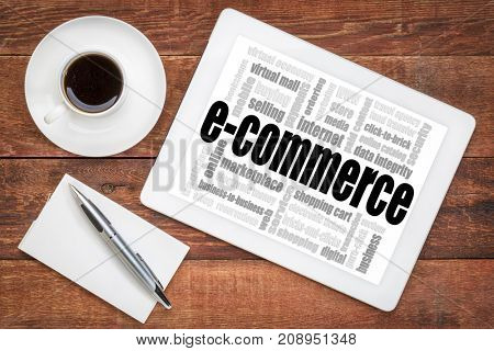 e-commerce word cloud - a digital tablet on a rustic wooden table with a cup of coffee