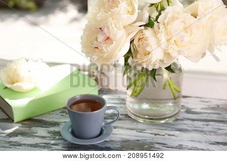 Cup of tea and vase with beautiful peony flowers on windowsill