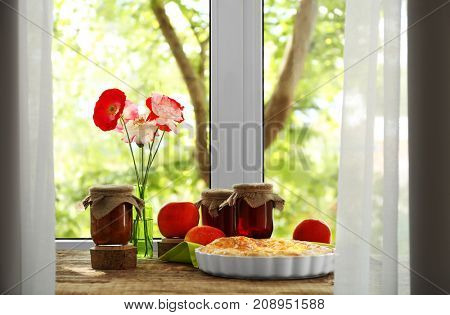 Delicious pie and jars with jam on windowsill
