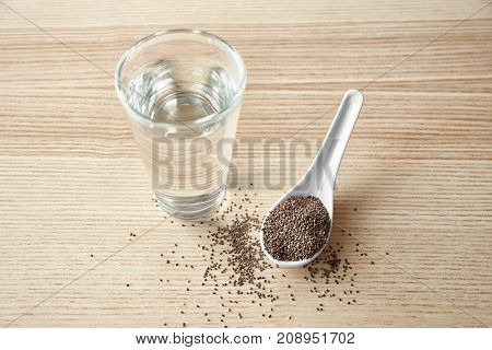 Spoon with chia seeds and glass of water on wooden background