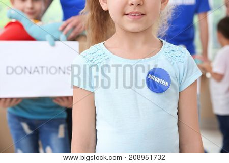 Little girl in shirt with volunteer button on blurred background