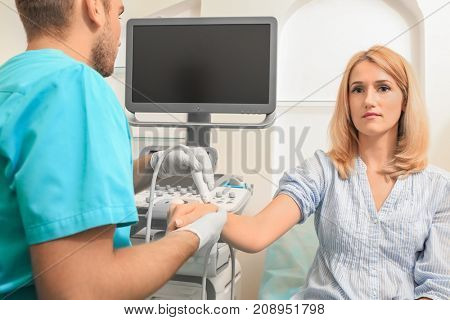 Doctor conducting ultrasound examination of patient's wrist in clinic