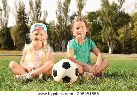 Cute children with soccer ball on lawn