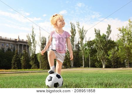 Cute girl with soccer ball on lawn