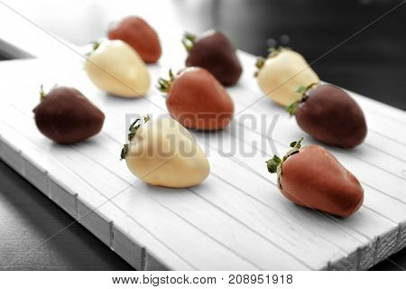 Board with tasty glazed and chocolate dipped strawberries on table, closeup