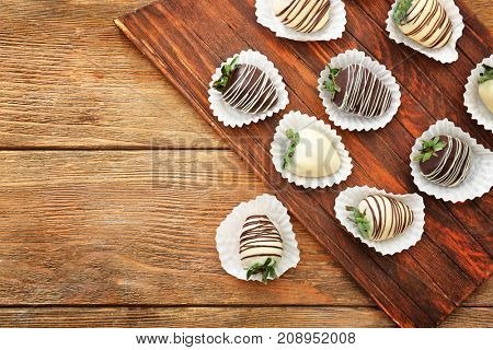 Tasty chocolate dipped strawberries on wooden board
