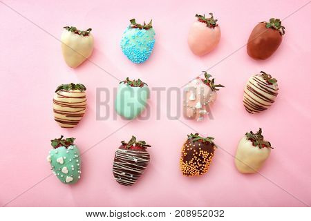 Tasty glazed and chocolate dipped strawberries on color background