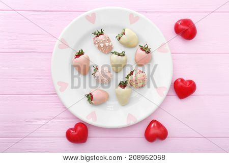 Plate with tasty glazed strawberries on wooden table