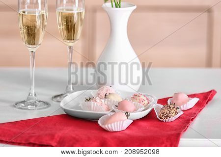 Plate with tasty glazed strawberries and glasses of champagne on table