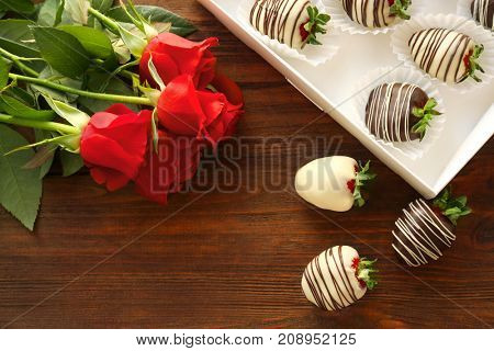 Box with tasty chocolate dipped strawberries and bouquet of flowers on table