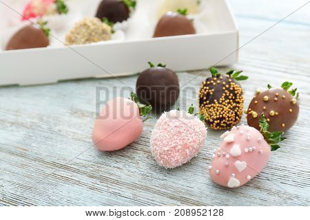 Tasty chocolate dipped and glazed strawberries on wooden background
