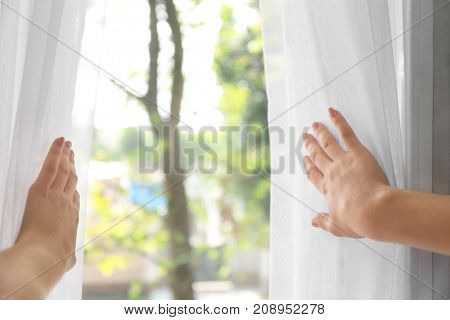 Woman opening beautiful white curtains indoors, closeup