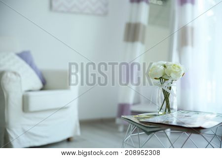 Bouquet of flowers in vase on table in light interior