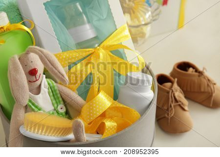 Cardboard box with baby shower gifts on table