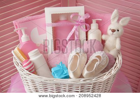 Wicker basket with baby shower gifts indoors