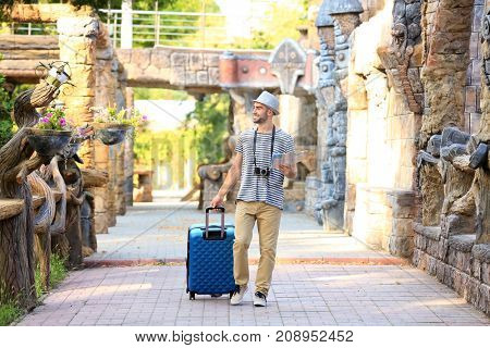 Handsome young tourist with map and suitcase near ancient castle