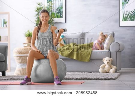 Beautiful young woman training at home